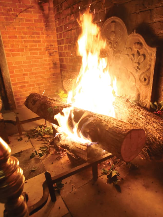 Yule logs burning in a large brick fireplace with sprigs of holly tossed around the logs