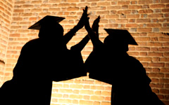 Shadow of two students in cap and gown high-fiving