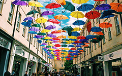 Rainbow umbrellas hang over an alley way