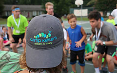 A student wears a hat with the Camp Kesem logo