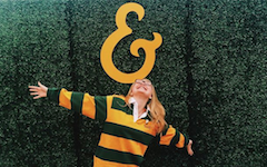 A student dressed in green and gold stripes opens her arms below a gold ampersand.
