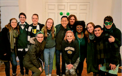 A group of friends, dressed in green and gold, stand together in the hallway of the Wren building.