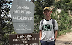 A student poses in front of a hiking post, surrounded by green wilderness.
