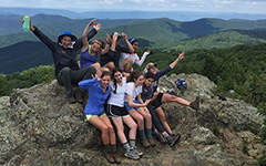 A group of nine students in hiking gear posing together on a boulder with their arms in the air with a view of wooded mountains and blue sky behind them.