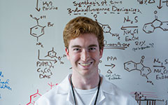 Smiling student standing in front of a white board with chemistry content on the board.