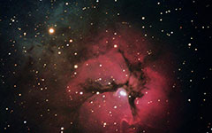 Trifid Nebula viewed through a telescope - The red region is an area of ionized hydrogen where stars are forming and the blue region is a cloud of dust particles that reflect the light from nearby stars