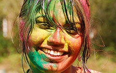 Smiling student face with multi-colored holi paint all over it