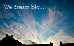 whispy clouds on a blue sky with the text We dream big...