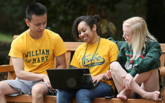 students on a bench using a laptop