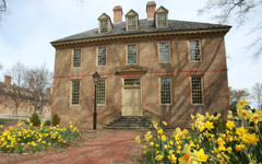The Brafferton: Historic brick building in early spring with many blooming daffodils in front.