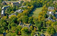 Aerial view of historic and old campus showing brick buildings, and open sunken garden and tree lined paths.