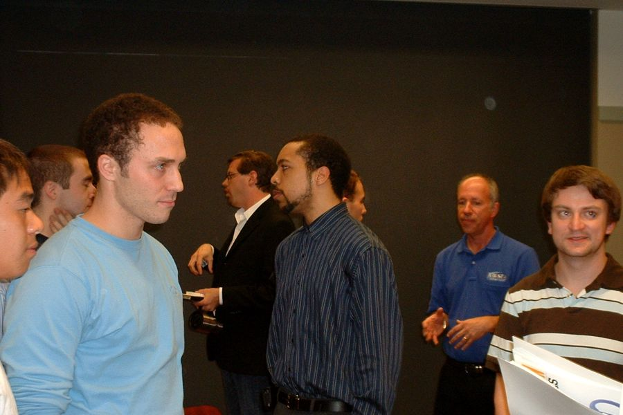 From left to right: panelists Jeremy Beker (M.S., '08, background), Carl Otto (B.S., '07) and Ben Ashton (background) mingle with attendees