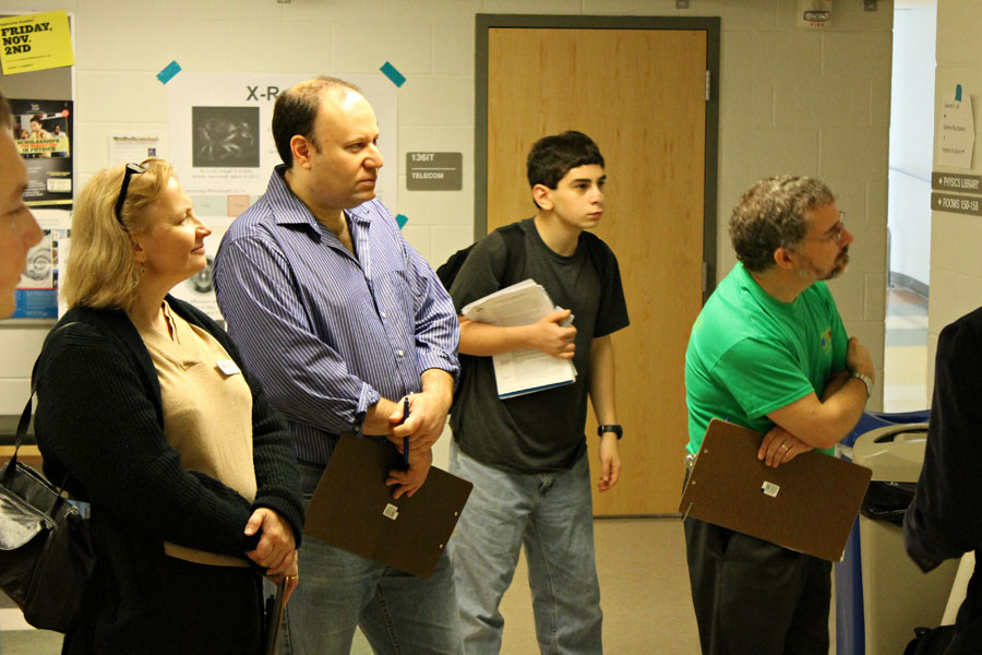 Judges examine a poster on undergraduate research during the poster session.  Photo credit J. Hill