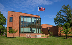 A brick building with large glass windows and an American flag on a flagpole