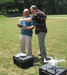 It takes two to use a quadcopter for research—one to fly the device (using the controller on the case) and a second to work a tablet, used for switching functions and monitoring the on-board camera. Gerard Chouin gives Sean Pada a little shade to get things started. Photo by Joseph McClain