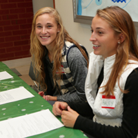 Soccer players Haley Kavanaugh (R) and Corinne Giroux registered volunteers at the toy and clothing distribution.