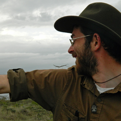 Jack Boyle, a Mellon Postdoctoral Fellow of Environmental Science and Policy at William & Mary, poses with a grass-mimicking stick insect in the Kenyan savanna.  (Photo courtesy Jack Boyle)