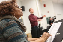 Composer Jeraldine Herbison concentrates on fine-tuning as Visiting Director of Choirs Miles Canaday directs a choir rehearsal of the song she wrote. (Photo by Stephen Salpukas)