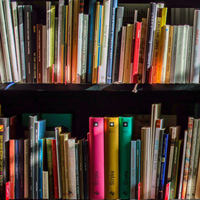 A bookshelf containing many books of various sizes and colors
