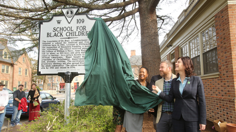 Jody L. Allen, director of the Lemon Project; Mark Kostro Ph.D. '18, senior staff archaeologist for the Colonial Williamsburg Foundation; and W&M President Katherine A. Rowe help to unveil the historical marker for the Bray School. (Photo by Stephen Salpukas)
