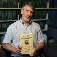 History Professor Christopher Grasso holding one of his books