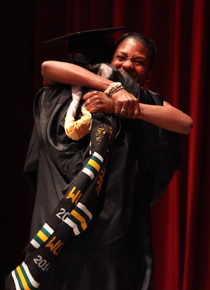 A graduate and loved one embrace during the 2014 Donning of the Kente ceremony. (Photo by Stephen Salpukas)