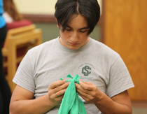 A student works on tying a shirt together to make a bag. (Photo by Stephen Salpukas)