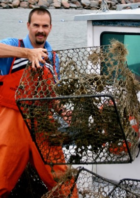 """Dave Stanhope, CCRM research manager, handles a derelict or """"ghost"""" crab pot recovered from the York River. (Photo by D. Malmquist/VIMS)"""