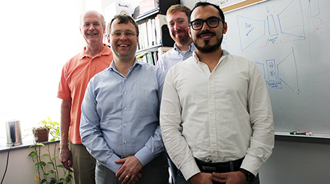Team of computer scientists stands in front of whiteboard