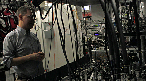 Seth Aubin, associate professor of physics at William & Mary, stands in front of a table of lenses, mirrors and other optics that his team uses to manipulate light to cool rubidium and potassium atoms.