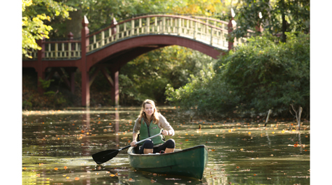 A person paddles a canoe in the Crim Dell pond