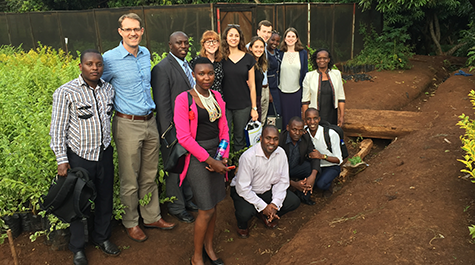 A team of students and faculty pose while touring the tour of Chuka University research garden.