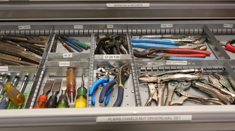 Tool drawer showing labeled compartments full of wrenches, screwdrivers, pliers