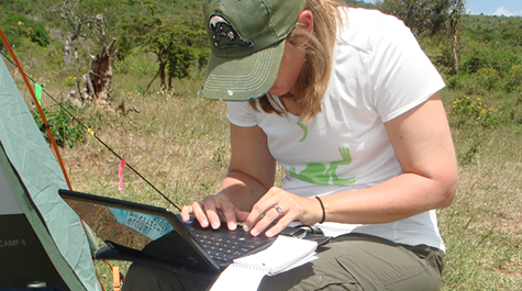 Carrie Dolan hunches over her computer taking notes in the field.