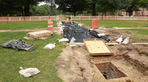 A hole in the ground near a construction area shows a vaulted brick drain