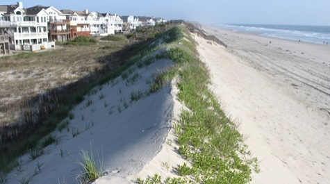 A sand dune with the beach visible on one side and houses on the other