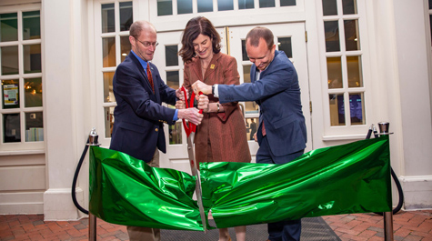 Three people use large scissors to cut a giant, green ribbon