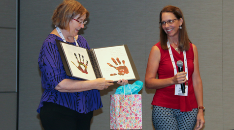 Heather Macdonald stands on stage and is presented with a book of SAGE 2YC Change Agent hand prints