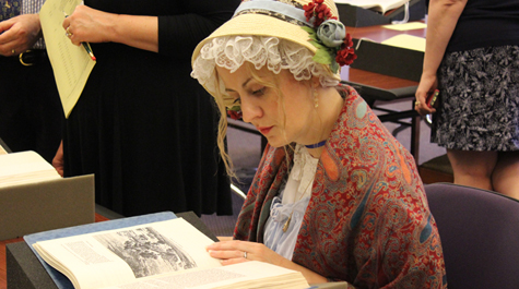 A person dressed in period clothing looks at a book