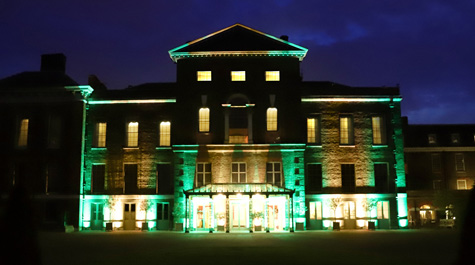 Gold and green lights shine on Kensington Palace at night