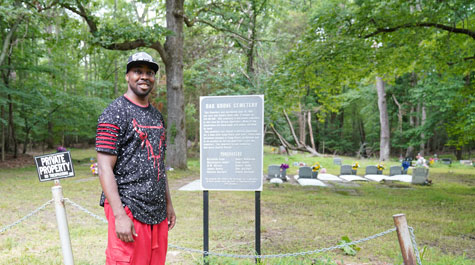 Travis Harris stands in front of gravestones at Oak Grove Cemetery