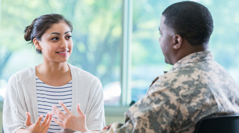 A counselor talks with a member of the military