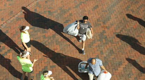 Aerial view of two people moving items into dorms