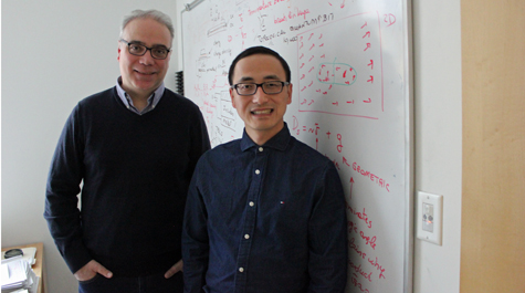 Enrico Rossi and Xiang Hu stand in front of a whiteboard