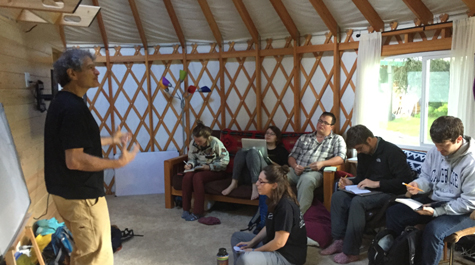 Students listen to lecture while sitting in yurt
