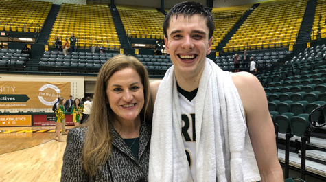 Huge with men's basketball captain Paul Rowley after Senior Day win over UNC-Wilmington