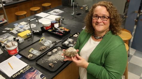 William & Mary archaeologist Jennifer Kahn examines artifacts from one of her numerous excavations of human sites in the islands of Oceania.