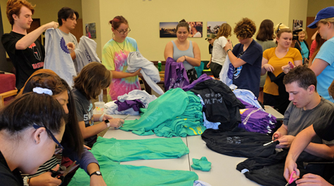 Students work on cutting up and tying together shirts around a table