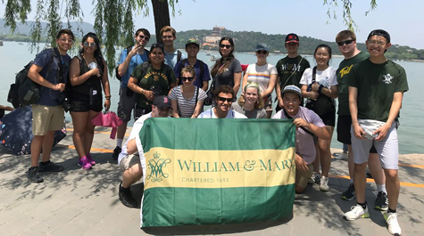 Students pose for a photo together on a beach and holding a William & Mary flag