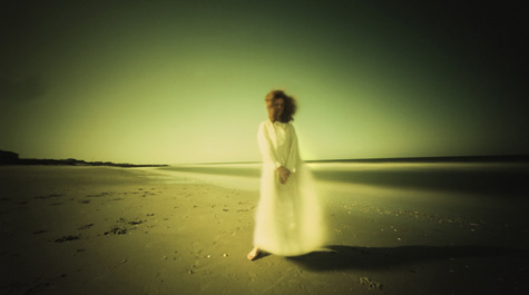 A person in a long, white gown stands on a beach